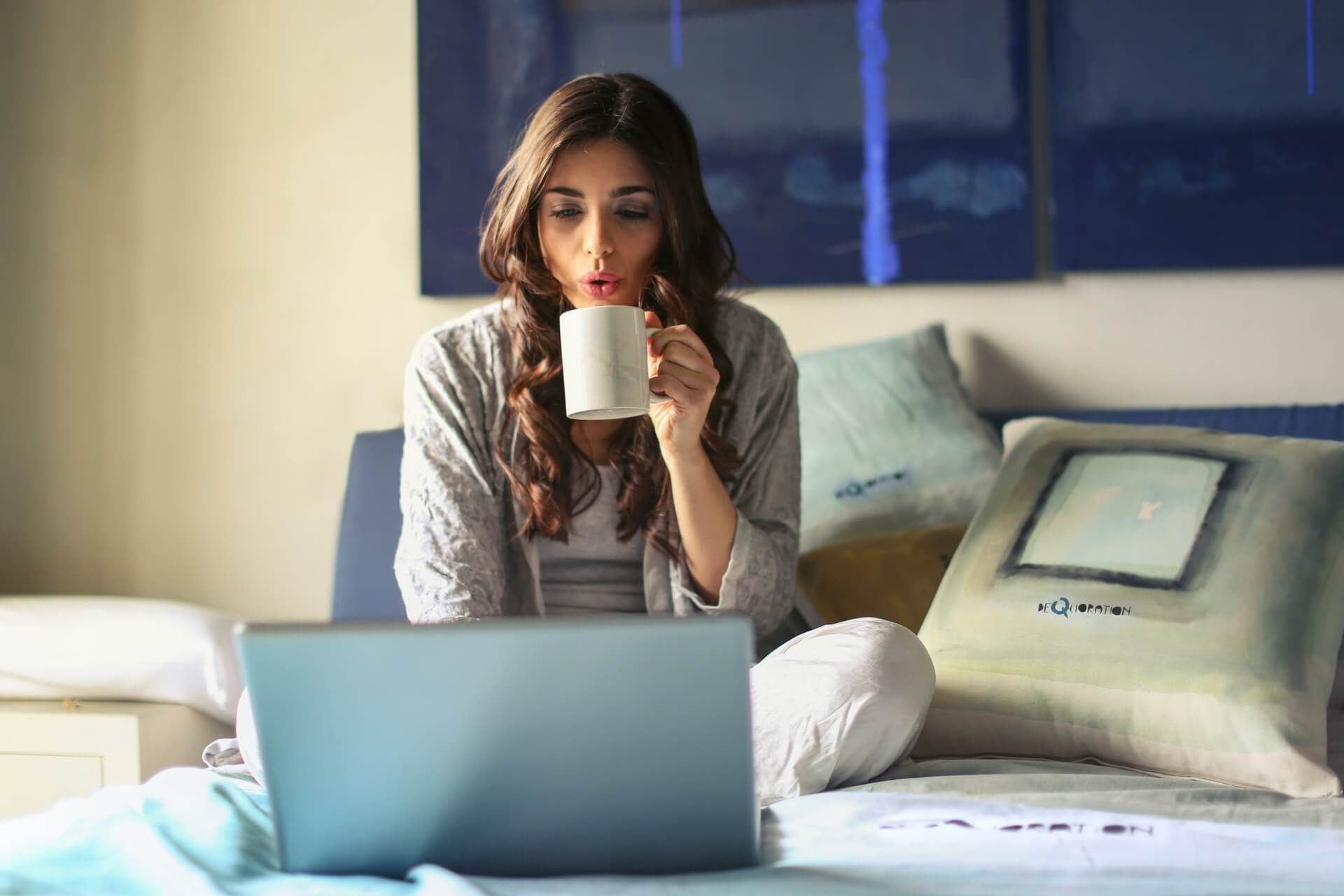 Woman sitting on bed using laptop and drinking coffee using an online chat room.